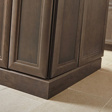 Close up of baseboard moulding on gray-brown cabinets