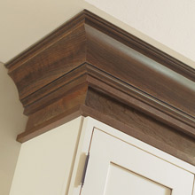 Off white cabinets with dark brown stained cabinet moulding