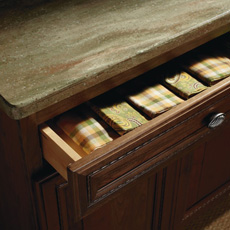 Cabinet drawer partially open to show linens inside