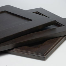 Stack of recessed panel cabinet doors in dark wood tones