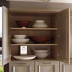 A frameless cabinet open with bowls on shelves