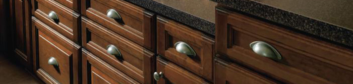 Close-up of base cabinets in a medium brown wood stain with cup pulls