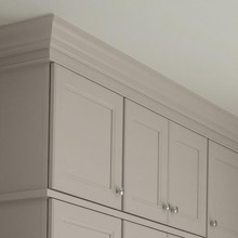 Cabinet moulding and hardware on light gray kitchen cabinets