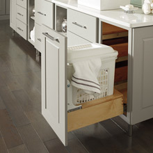 Light gray bathroom cabinets with a hamper cabinet pulled out to show basket inside