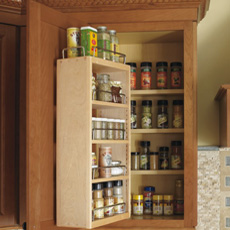 Wall cabinet open to show spice racks built inside door