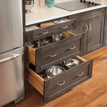 Three drawer base cabinet in kitchen with drawers open to show storage