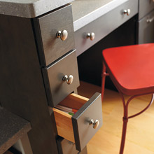 Close up of office area in kitchen with spice drawers for storage