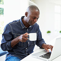 Man drinking coffee and using laptop