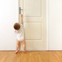 Child trying to open a closed door