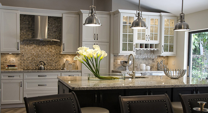 Remodeled kitchen with off white cabinets and a dark Maple island>
