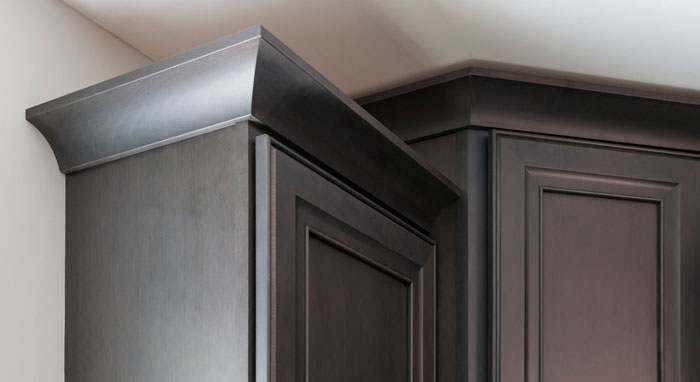 Close-up of crown moulding on gray kitchen cabinets>