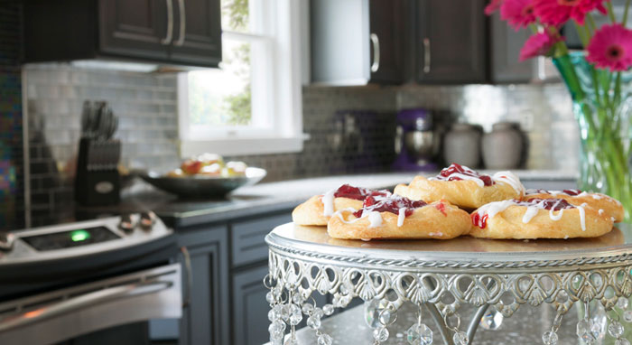 Close-up of pastries on cake stand in remodeled kitchen>