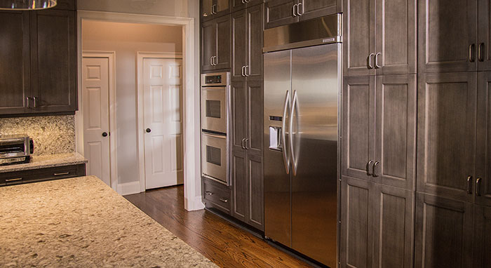 Double oven cabinet and tall storage cabinets in remodeled kitchen>