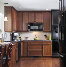 Renovated kitchen with dark cherry and maple wood cabinets by Homecrest