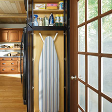 Laundry room utility cabinet with ironing board and cleaning supplies