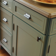 Industrial-like metal cabinet hardware on green cabinets