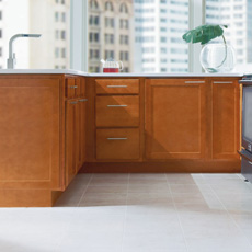 L shape configuration of base cabinets in a medium wood finish