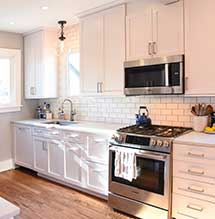 Small kitchen renovated with white cabinets by Omega